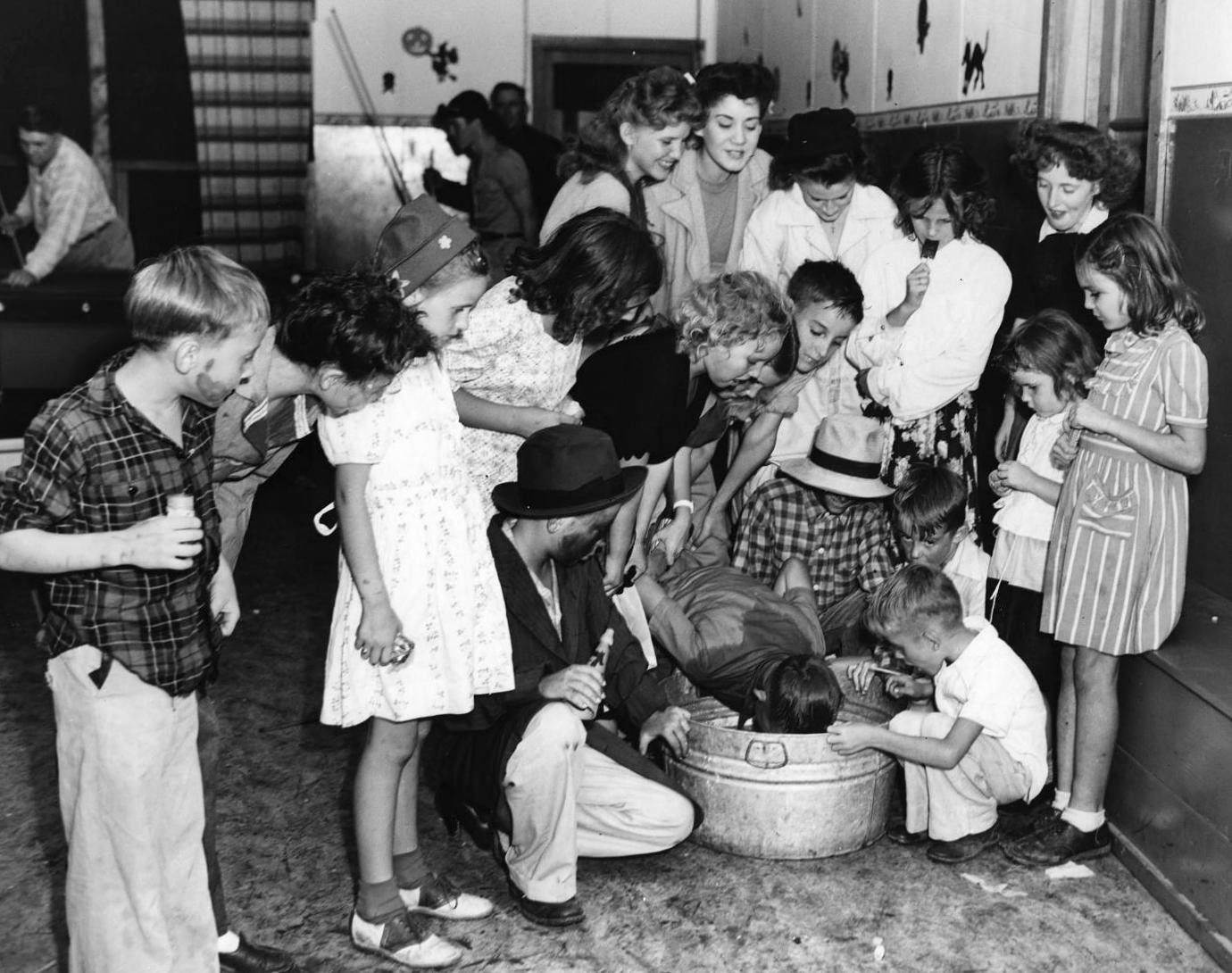 "dunking for apples at a halloween night ""spooks' party"" 